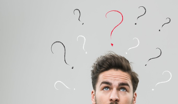 A man looks up as question marks surround his head.
