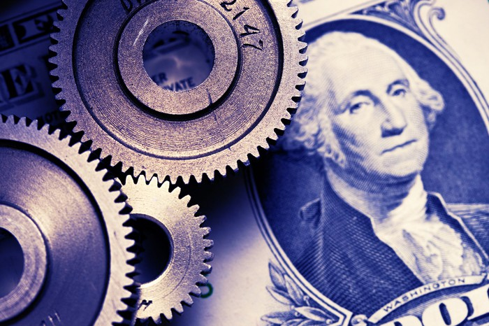 A collage with gears and a one dollar bill