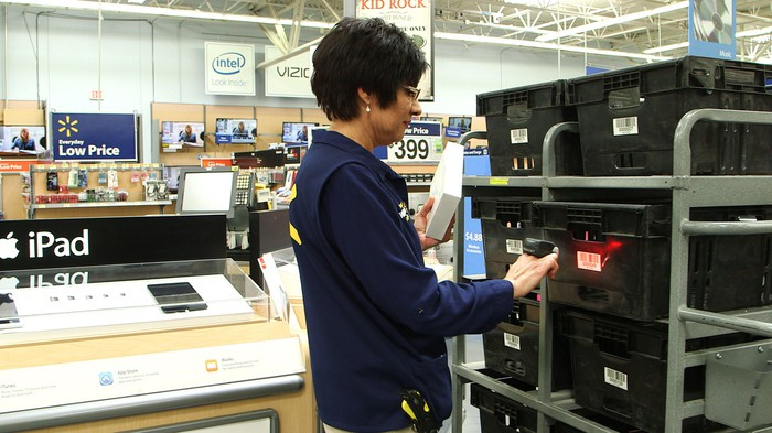 A worker prepares a digital order at Wal-Mart.