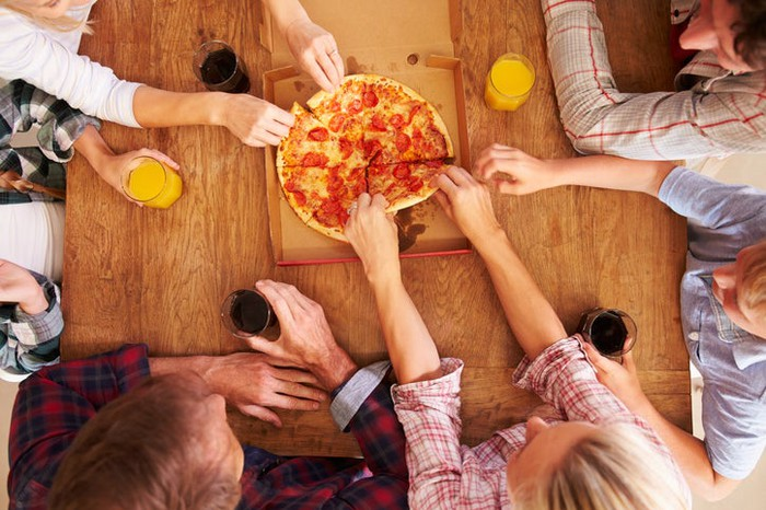 People sharing pizza at a table