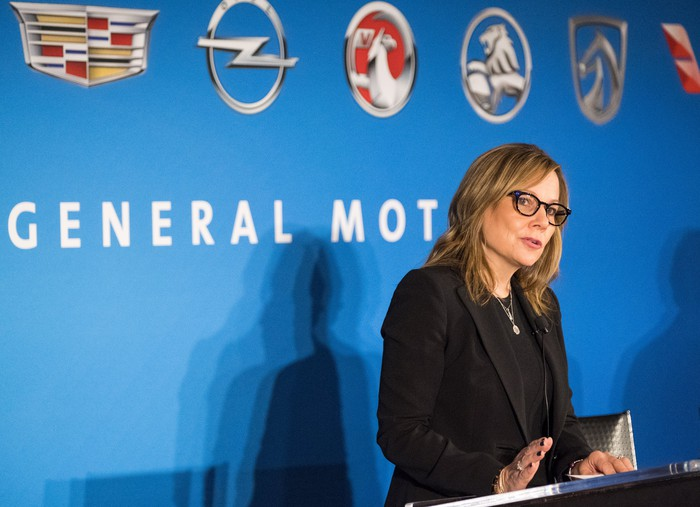 Mary Barra speaking before a GM-logoed backdrop.