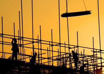 constructions workers building at sunset silhouettes