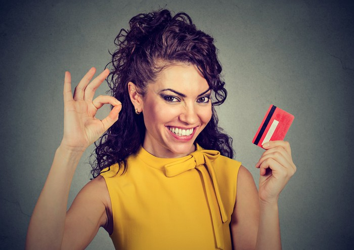 Woman smiling, holding credit card and making okay sign with fingers