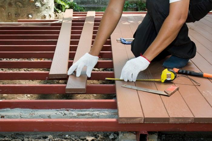 Worker installing wood decking.