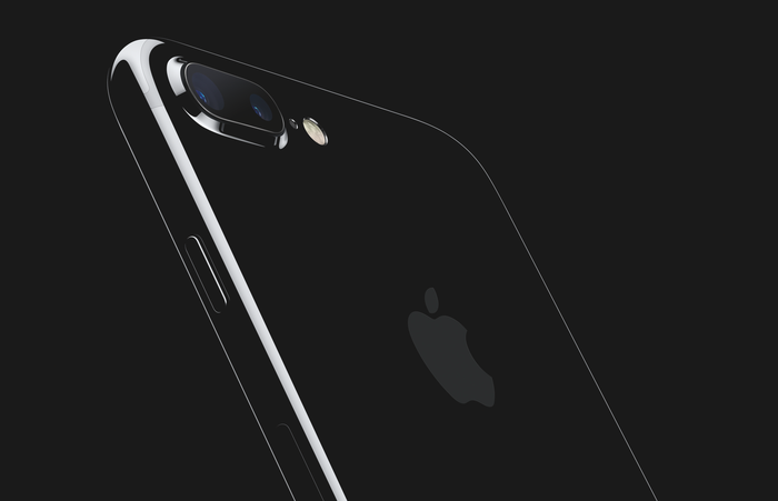 A view of Apple's new jet black iPhone 7 shimmering in front of an all black background