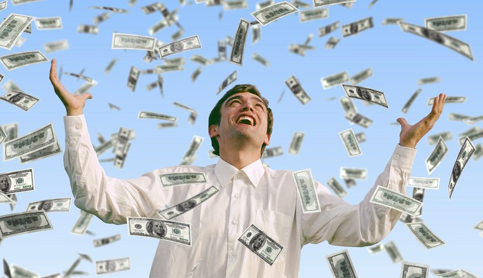 """Man smiling at the sky as money """"rains"""" down on him."""
