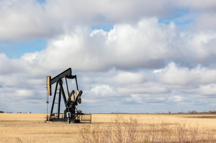 An oil well stands in a rural field, with a cloudy sky in the background.