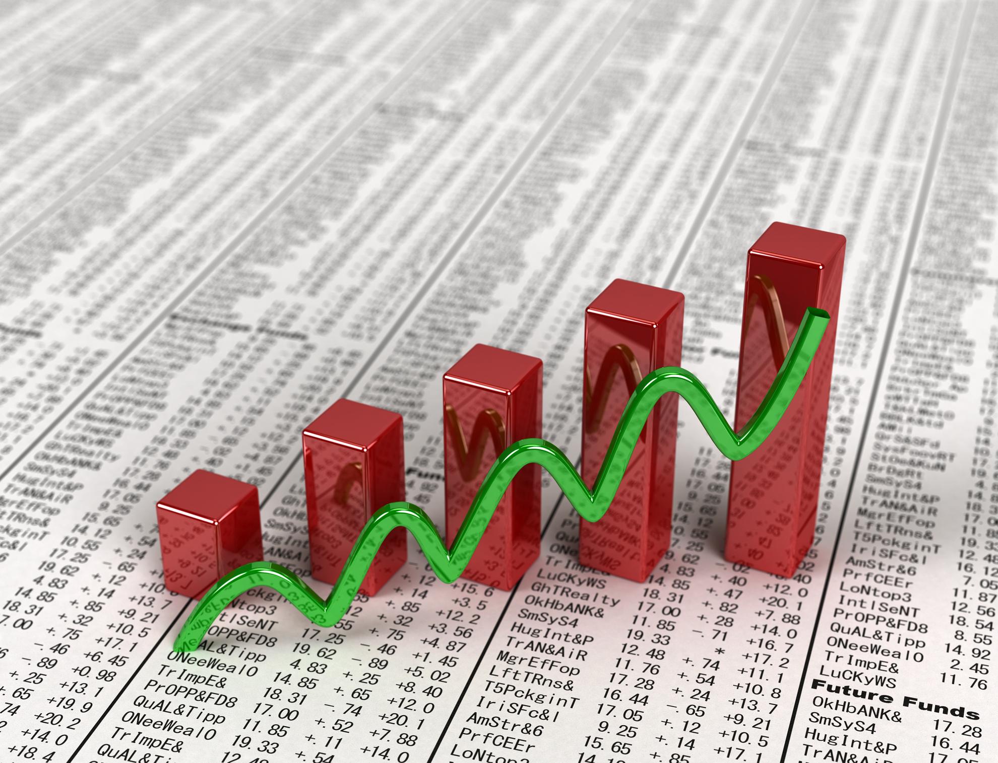 A rising chart atop a financial newspaper.