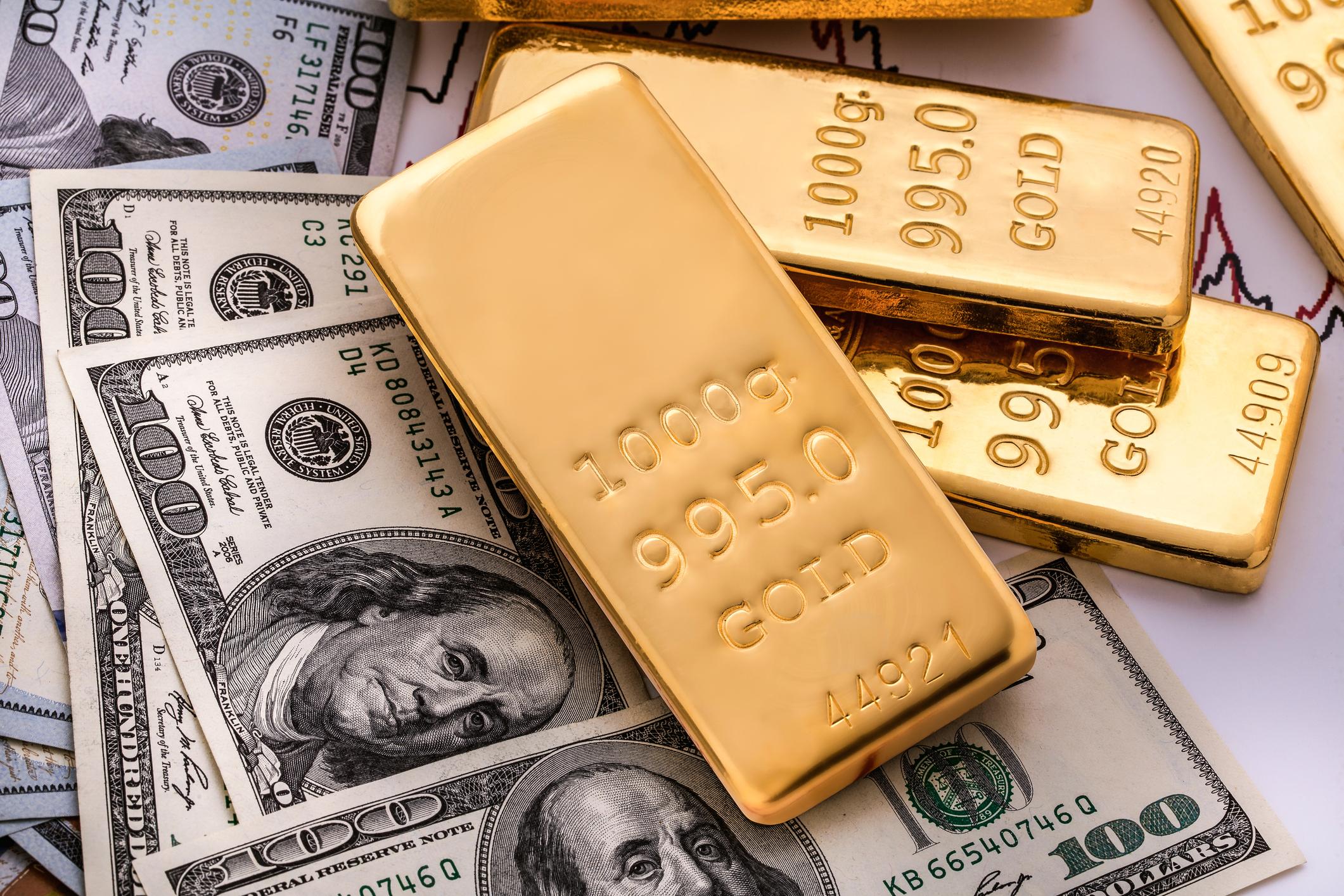Gold bars rest atop one-hundred-dollar bills.