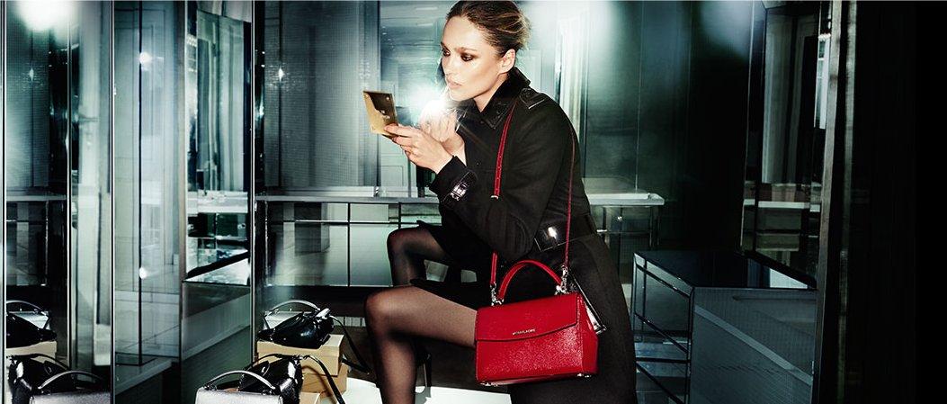 A woman wearing a Kors handbag applies makeup.