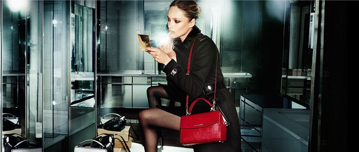 A woman wearing a Kors handbag applies makeup.