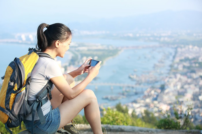 Woman using her smartphone, overlooking a bustling metropolis from an idyllic hilltop.