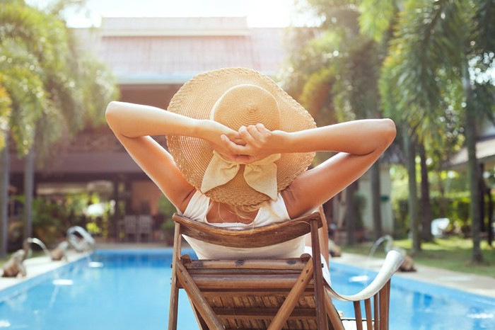 A woman relaxes by a luxury hotel poolside in the summer.