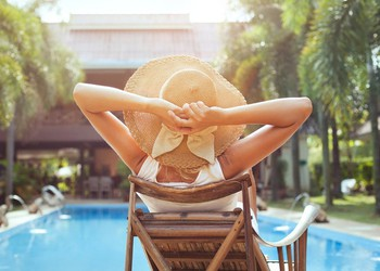 Woman Relaxing At Luxury Hotel Pool