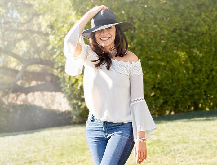 A model in Chico's clothes standing in a field with her hand on her hat