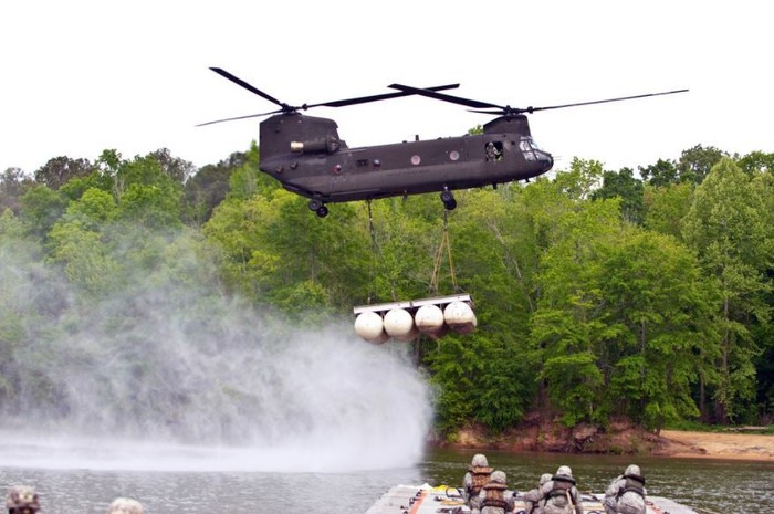 A CH-47 Chinook carrying an object over a body of water.