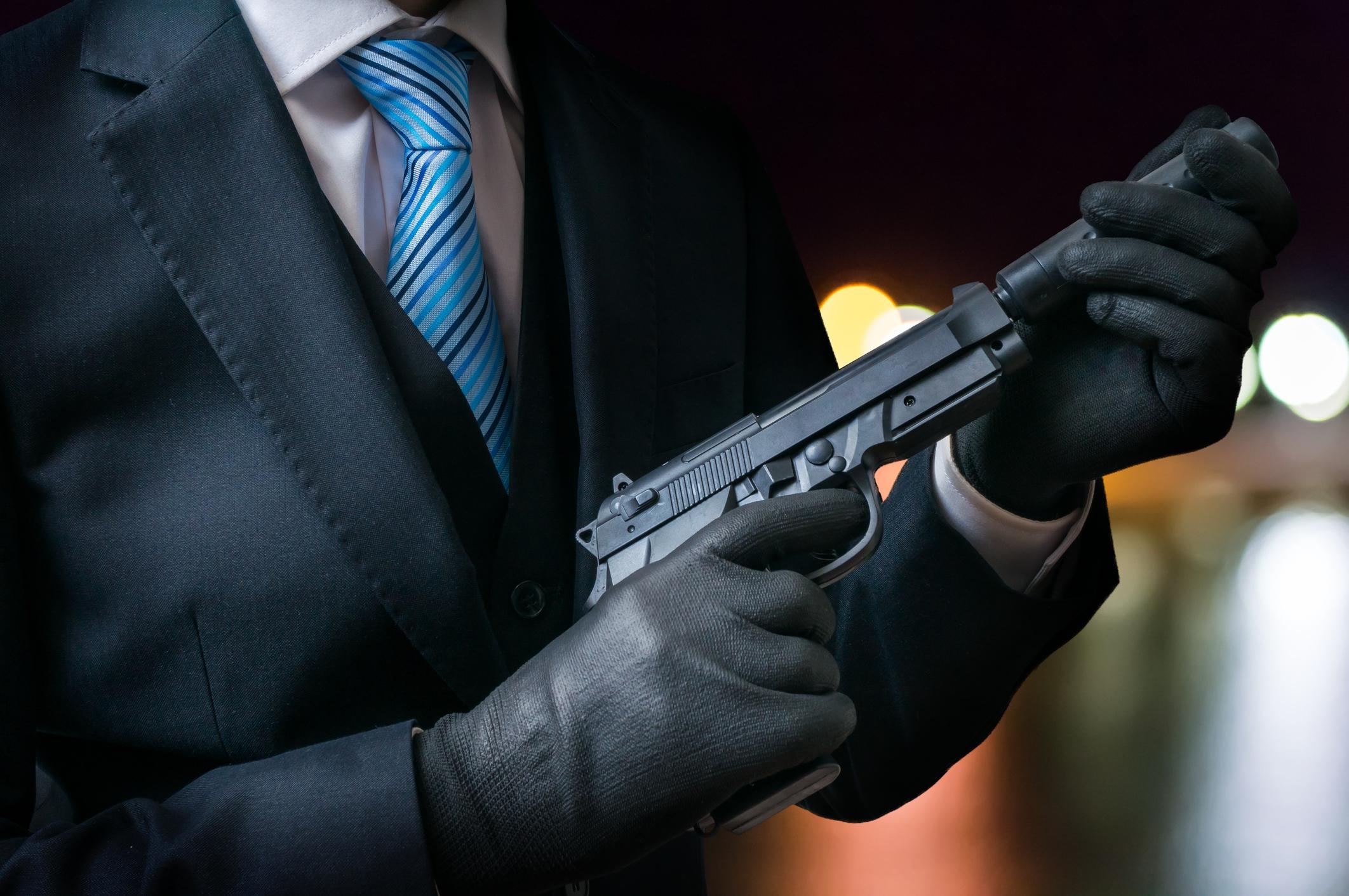 A killer putting a silencer on a gun.