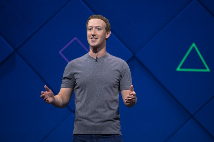 Mark Zuckerberg speaking on stage before a blue backdrop.