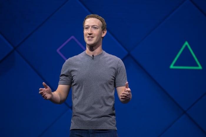 Mark Zuckerberg speaking on stage before a blue backdrop.