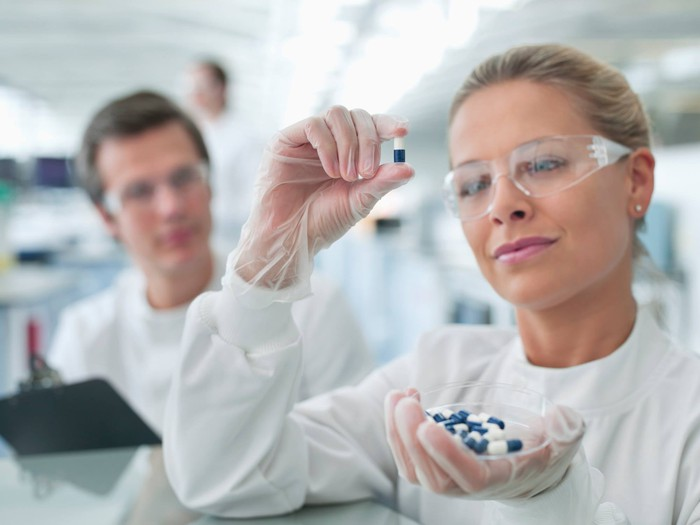 Woman in white lab coat and gloves holding a container of blue and white capsules in one hand and a single capsule in another, as a man in a lab coat with a clipboard looks on.