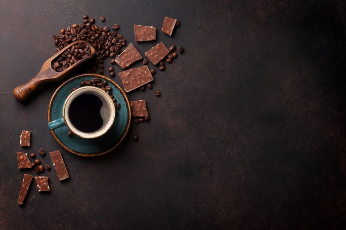 Overhead view of a coffee cup with coffee beans around the table.