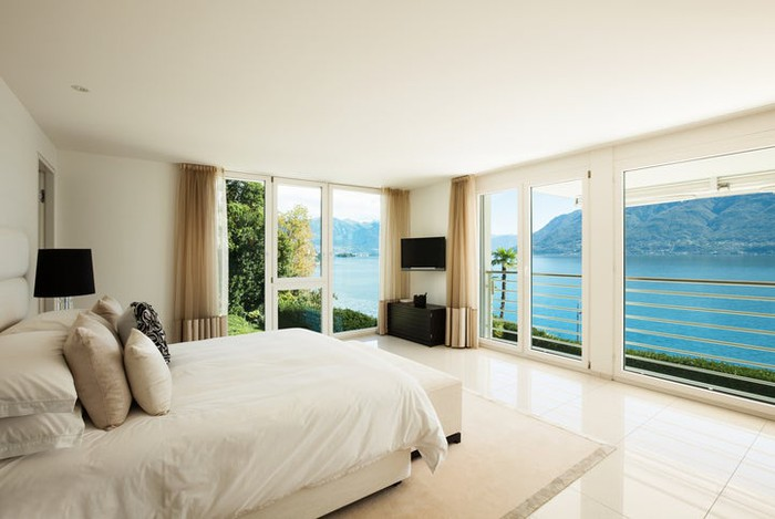 A hotel room overlooks a body of water.