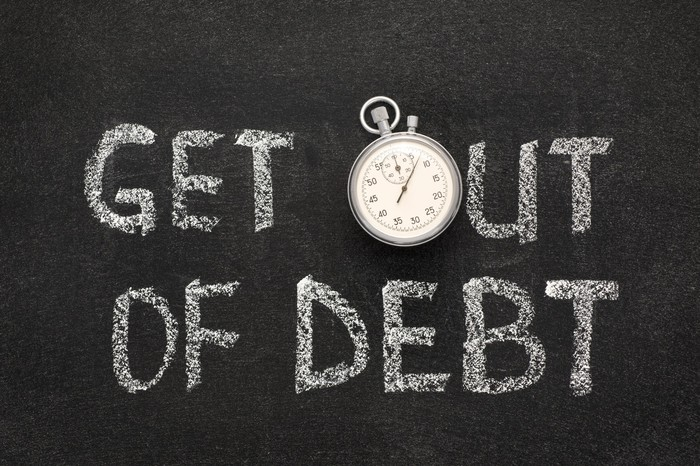 """""""Get out of debt"""" is written on a chalkboard, with a stopwatch used in place of the """"O"""" in """"out."""""""