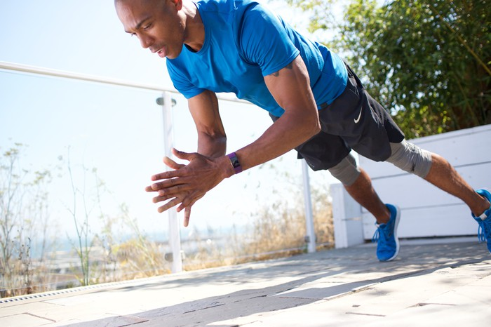 Fitness trainer demonstrating a clapping pushup with a Fitbit Blaze on his wrist.