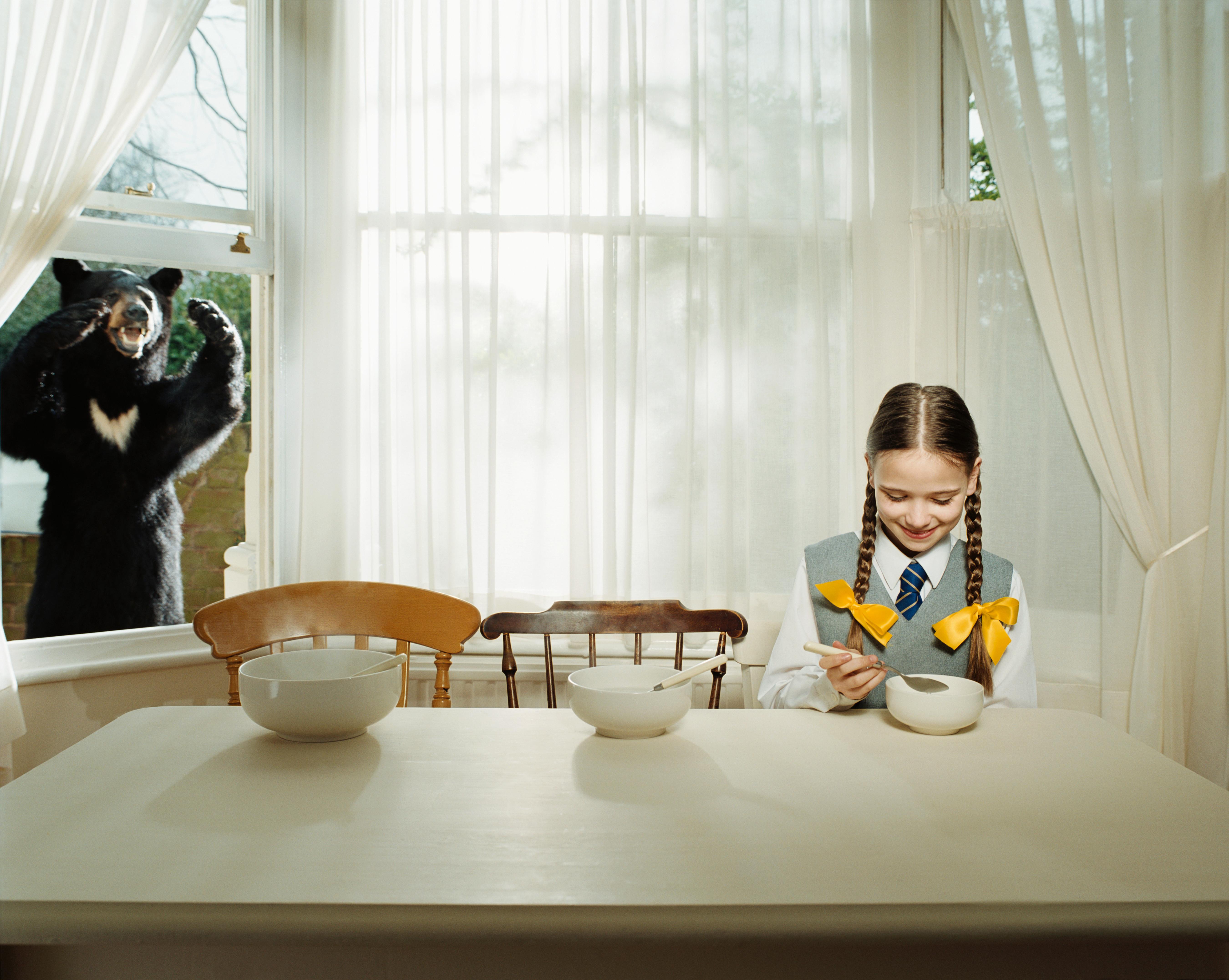 Goldilocks eats porridge while a bear looks through a window.