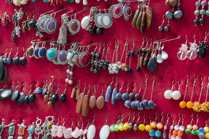 Multiple pairs of earrings are pinned to a red board.