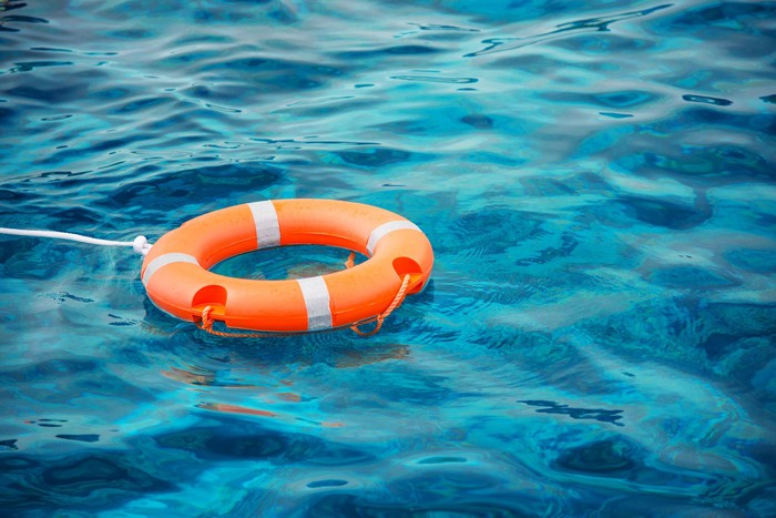 A life preserver buoy ring floats on the water.