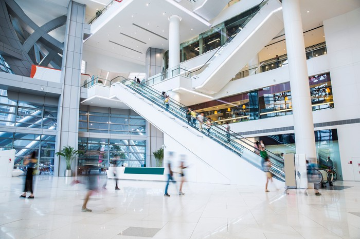 Shoppers walk through the inside of a mall, with an escalator in the background.