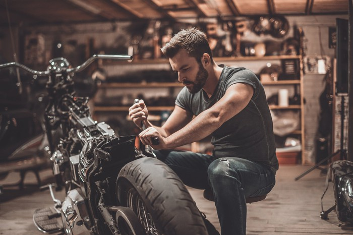 A man works on a motorcyle in a garage.