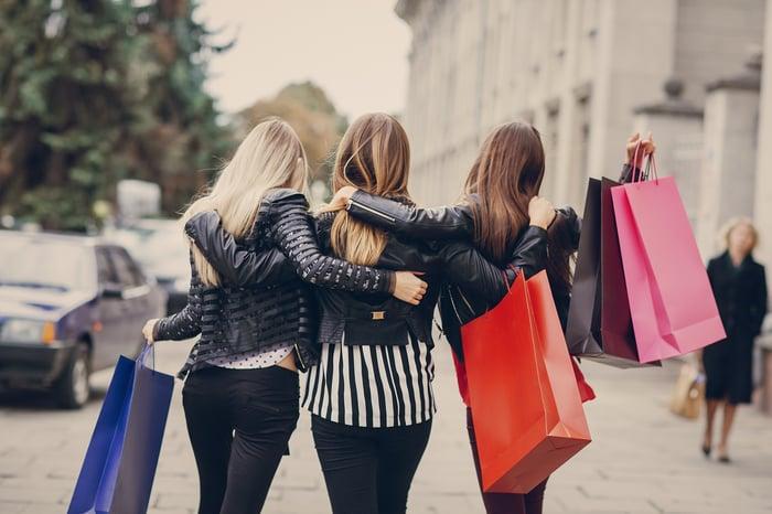 Three women walk away, arm in arm, holding shopping bags.