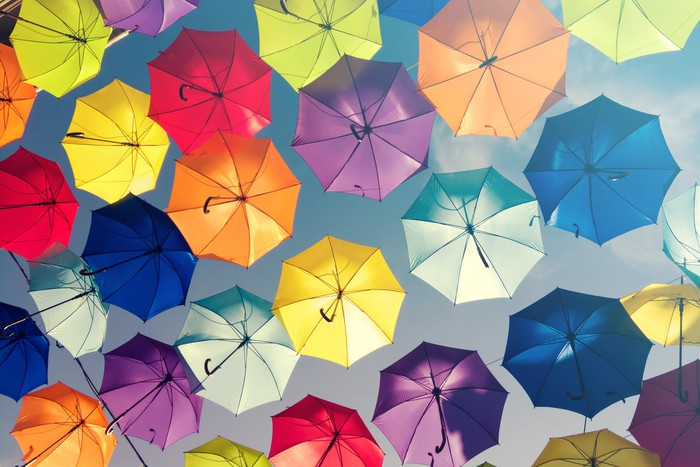 Several colorful umbrellas are opened, with a blue sky above them.