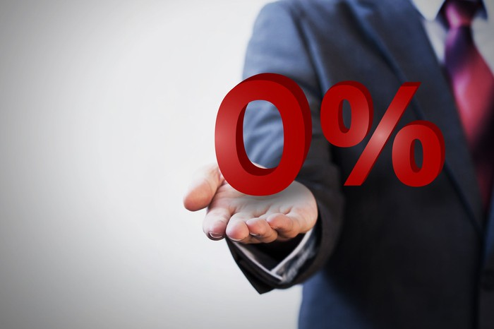 Man in suit holding out hand on which is a big red 0% sign