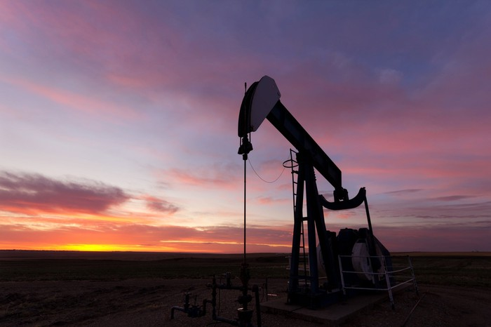 A close up photo of an oil well silhouette with a beautiful sunrise above the distant horizon.
