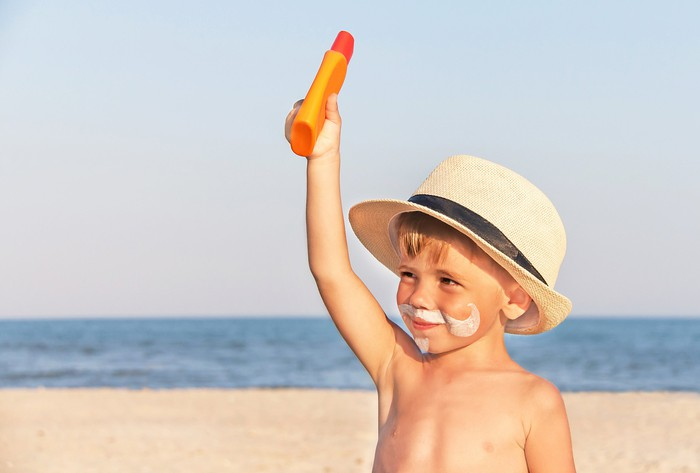 A young kid with a sunscreen beard on the beach.