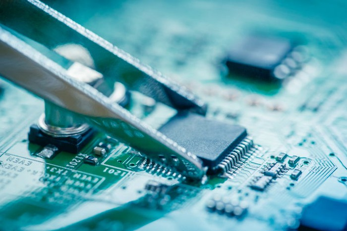 A set of tweezers touches a semiconductor on a device's logic board.