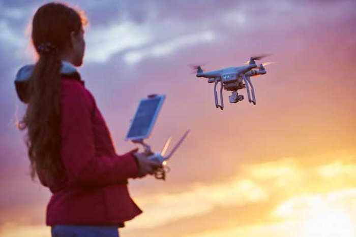 Image of a girl flying a drone.