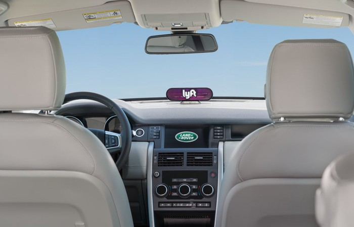 The interior of a Land Rover with a Lyft sign visible.