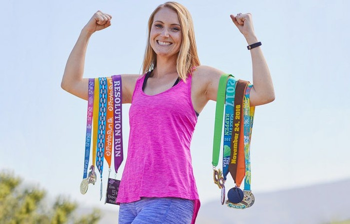 A woman holding her arms up with medals hanging off of them
