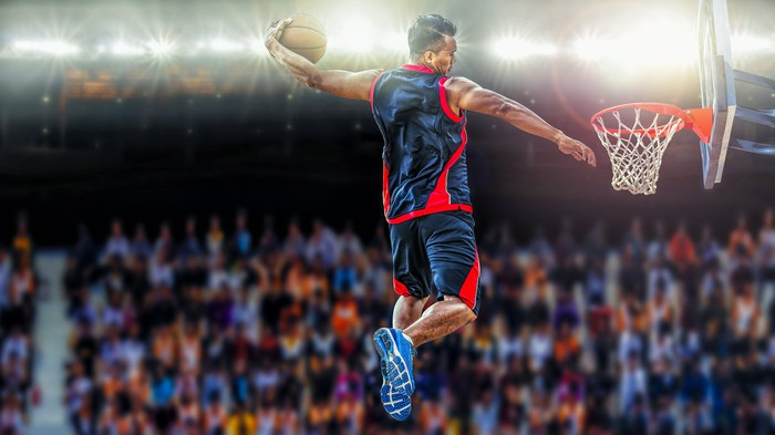 A basketball player prepares to score an athletic slam dunk shot.