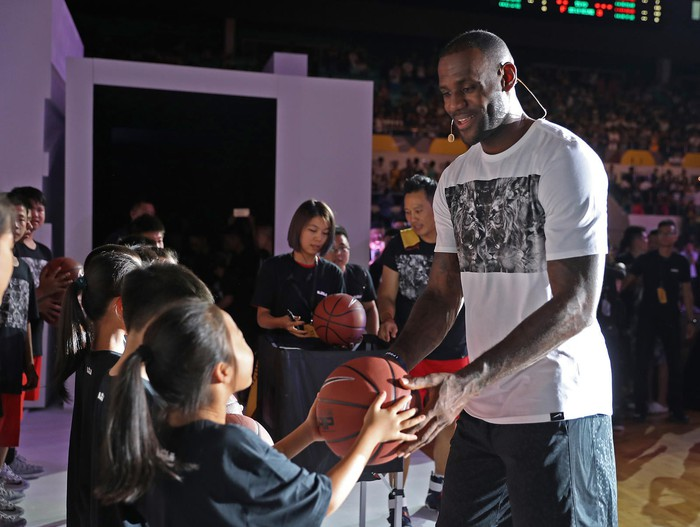 LeBron James hands a young fan a basketball.