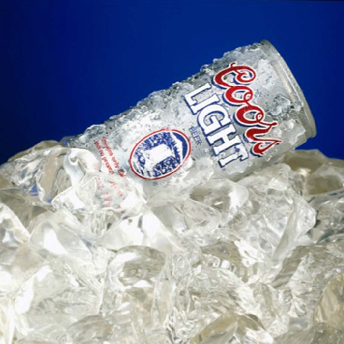 A can of Coors Light sitting on top of a pile of ice.