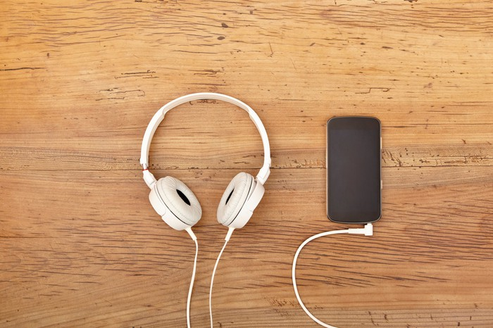 White headphones sitting next to a smartphone.