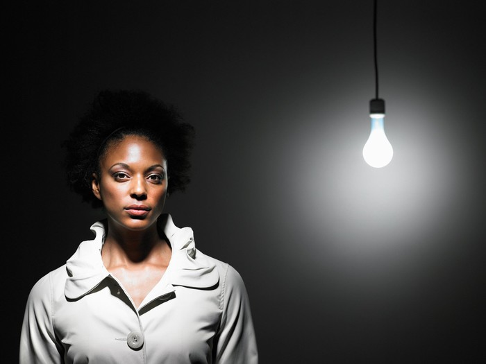 Woman standing near a light bare lightbulb.