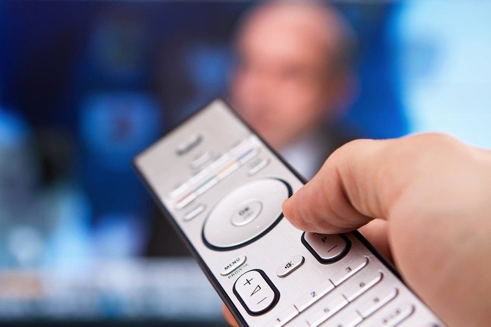 A hand points a TV remote at a screen.