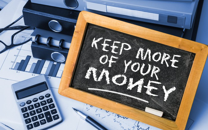 """Keep more of your money"" is written on a chalkboard, with a pen, calculator, glasses, graphs, and binders surrounding it."
