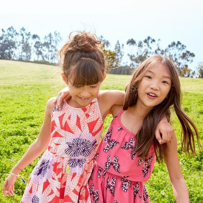 Two girls playing in a field wearing Gymboree dresses.